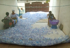 Workers cleaning used water sachets credit Douglas Bruce
