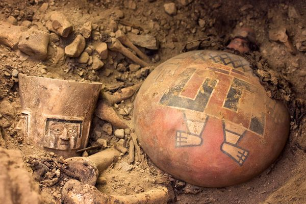 Photograph by Patrycja Przadka Giersz.  As archaeologists dug in one side chamber, they unearthed the remains of a Wari queen and several regal offerings, including a brilliantly painted ceramic flask (right) and an alabaster drinking cup (left).
