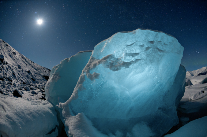 """2009 Jökulsárlón, Iceland. Destined to melt, an 800-pound chunk of ice glows in moonlight, from the National Geographic story """"Meltdown."""""""