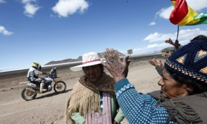 A Dakar rally competitor passes indigenous people between Bolivia and Chile. The rally, it is claimed, turns their land into a tourist attraction. Photo: Felipe Trueba/EPA