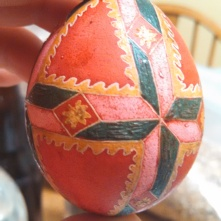 A finished egg with most of its wax still present to give texture and a stained glass effect