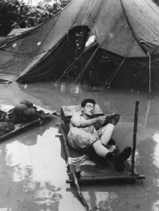 A soldier reads an Armed Services Edition in monsoon conditions during World War II. Australian War Memorial/Courtesy of Houghton Mifflin Harcourt