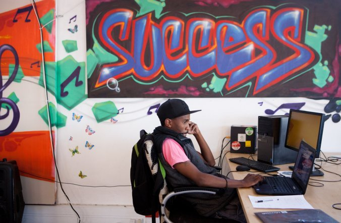 An entrepreneur uses his laptop near graffiti-decorated walls at Hubspace in the Khayelitsha township. Emily Jan/NPR