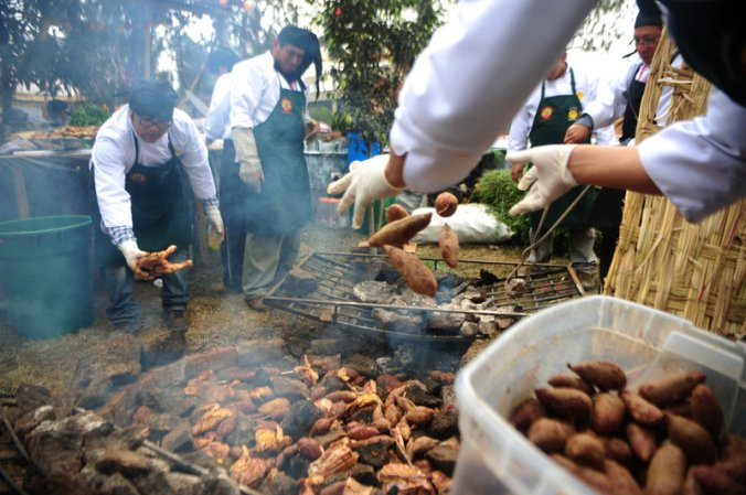 People throw potatoes into a pachamanca during a gastronomic fair Mistura in Lima. PHOTO: Ernesto Benavide