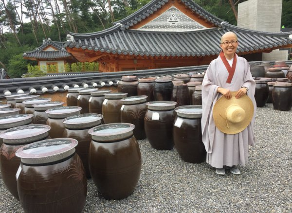 Sun Woo directs the visitor program at Jinkwansa, a Buddhist temple outside Seoul famous for preserving the art of Korean temple food. Behind her are giant jars filled with fermented soybeans. PHOTO:  Ari Shapiro/NPR