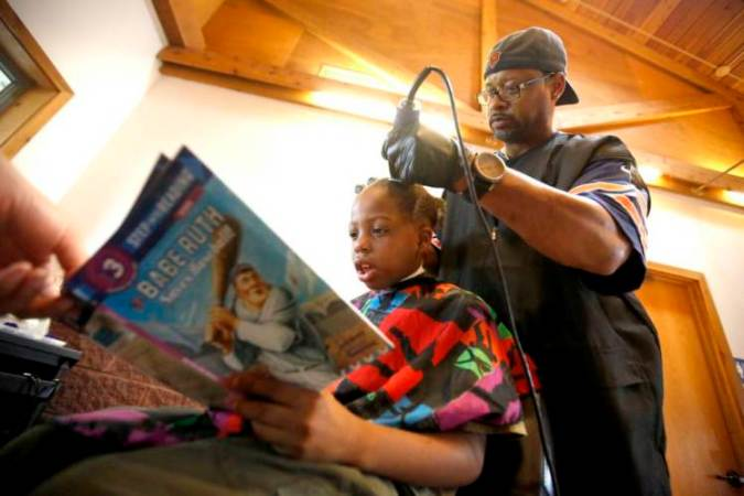 Courtney Holmes, right, listens to Jeremiah Reddick, 9, of Dubuque, as he reads while receiving a free haircut during the Back to School Bash in Comiskey Park, in Dubuque, Iowa. (Mike Burley/Telegraph Herald via AP)