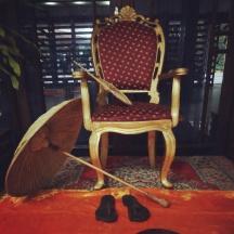 A throne, olakuda (umbrella made of palm fibre) and wooden sandals symbolize Mahabali's presence