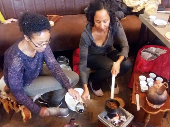 Luwam Melake (left), a recently arrived Eritrean refugee, and Saba Tesfay, who is half-Hungarian and half-Eritrean, wash, roast and grind coffee beans during a traditional Eritrean coffee ceremony. PHOTO: Lauren Frayer for NPR