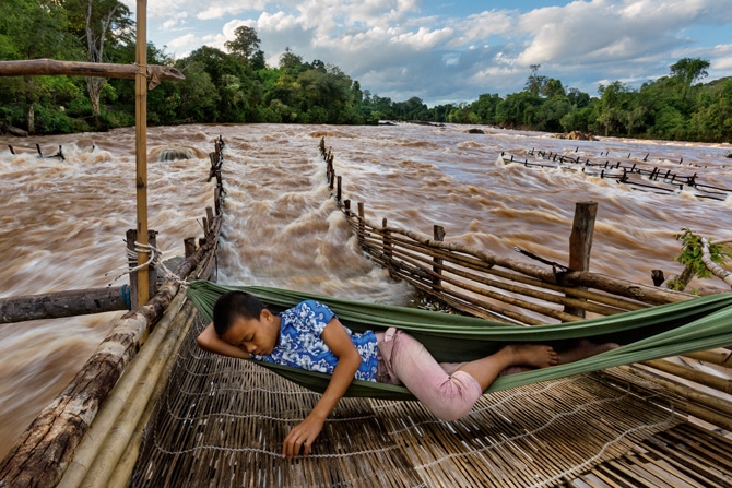 In southern Laos, near where the Don Sahong dam will soon rise, a fisherman's son snoozes above his father's weir, waiting for fish migrating upstream to tire and wash back into the trap. PHOTO: David Guttenfelder