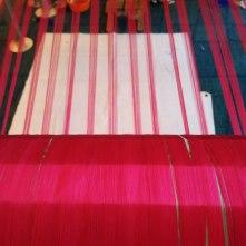 Pink silk thread on the loom