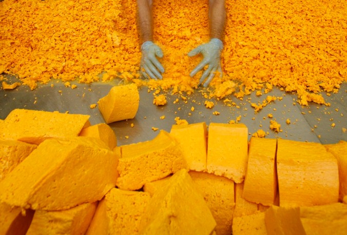 Cheesemaker David Clarke separates the curds and whey to make Red Leicester cheese at Sparkenhoe Farm in Upton